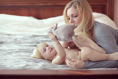Portrait of a mother with her baby in bedroom at home photo