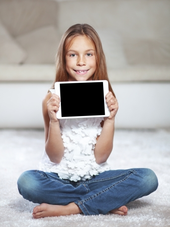 Child playing on tablet pc sitting on a carpet at home photo