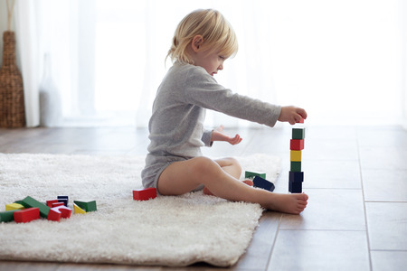 piramide humana: Niño jugando con bloques de madera en el hogar