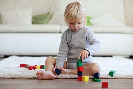 baby girl playing: Toddler playing with wooden blocks at home Stock Photo