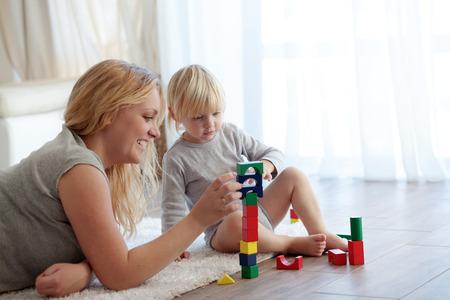 Madre con un niño jugando con bloques de madera en el hogar Foto de archivo - 23810305