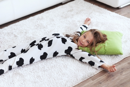 sofa bed: Portrait of child in soft warm cow print pajamas waking up at morning