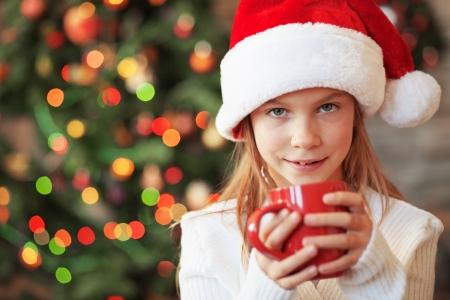 Tea tree: Portrait of a child drinking hot tea over Christmas tree lights