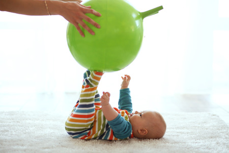 kids playing sports: Baby playing with gymnastic ball with mother at home
