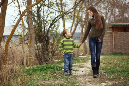 Young mother walking with her little son outdoors in autumn photo