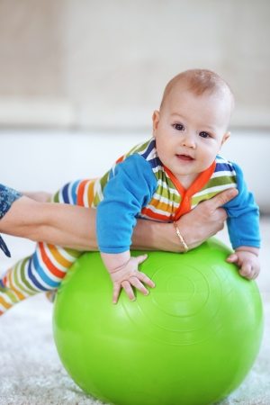 Baby playing with gymnastic ball with mother at home photo