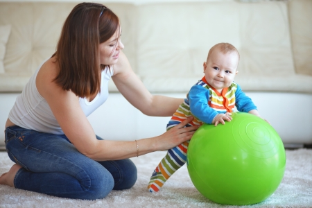 mum: Baby playing with gymnastic ball with mother at home