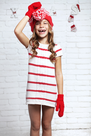 Little fashion girl in fashion Christmas clothes posing over white brick background, full length photo