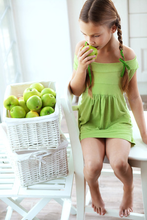 Cute little girl eating green apple in a rustic kitchen at home photo