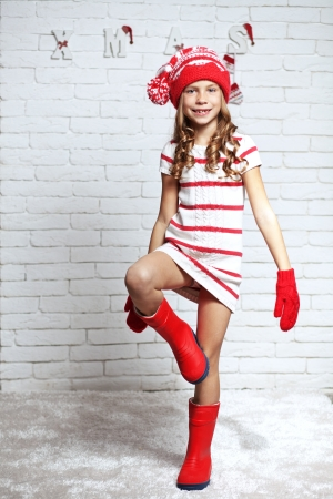 Little fashion girl in fashion Christmas clothes posing over white brick , full length photo