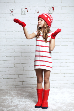 studio model: Little fashion girl in fashion Christmas clothes posing over white brick , full length Stock Photo