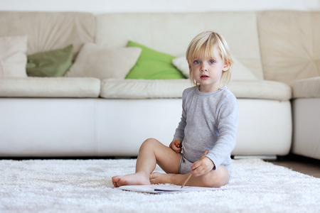 assiduous: Toddler drawing pictures sitting on a carpet at home