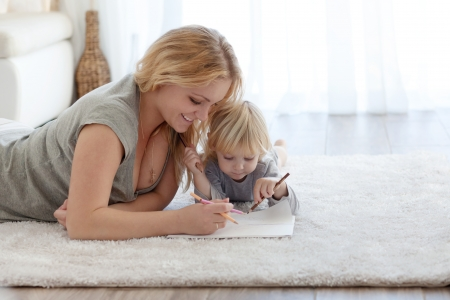 Mother with a child drawing together on a carpet at home photo