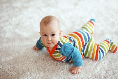 6 ヶ月赤ちゃんは居心地の良い柔らかいカーペットの上で横たわっているとカメラ目線