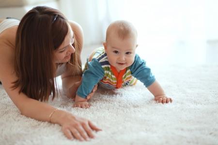 自宅のカーペットの上で遊んで彼女の赤ちゃんと母親 写真素材