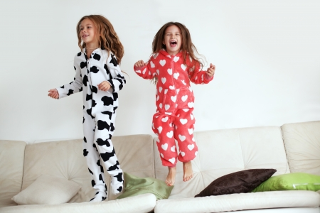 messy kids: Children in soft warm pajamas playing at home