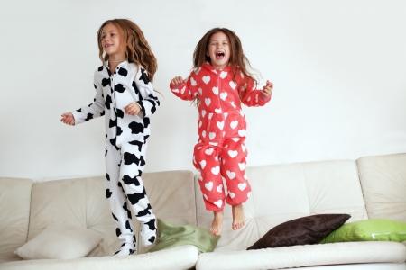 Kinderen in zachte warme pyjama spelen thuis Stockfoto