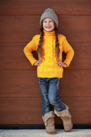 model posing: Cute little girl wearing knit winter clothes posing over wooden