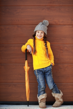 Cute little girl wearing knit winter clothes posing over wooden  photo