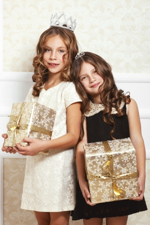 Portrait of luxury little girls with gold gift boxes Stock Photo