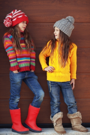 Cute little girls wearing knit winter clothes posing over wooden  photo