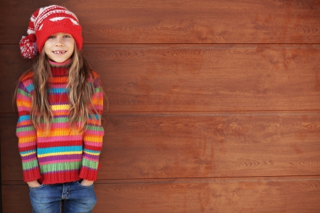 child model: Cute little girl wearing knit winter clothes posing over wooden