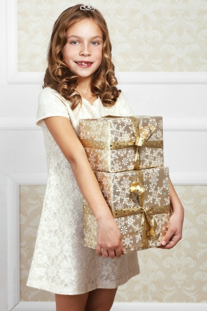 Portrait of luxury little princess with gold gift box photo