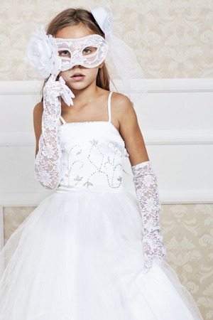 Portrait of a fashion girl wearing wedding dress and venetian mask photo