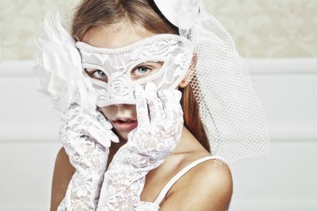 little model: Portrait of a fashion girl wearing wedding dress and venetian mask Stock Photo