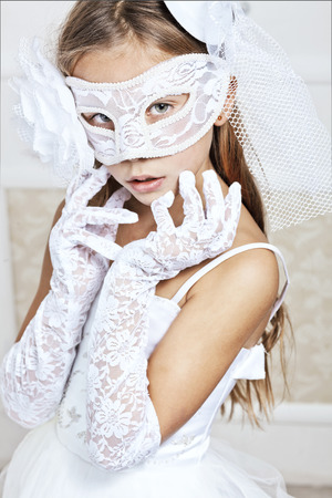 wedding portrait: Portrait of a fashion girl wearing wedding dress and venetian mask Stock Photo