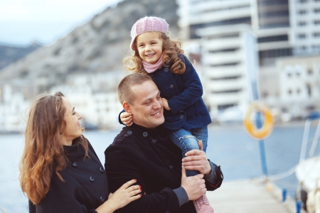 urban parenting: Portrait of happy young family walking with their child on berth near sea in the city, still life photo