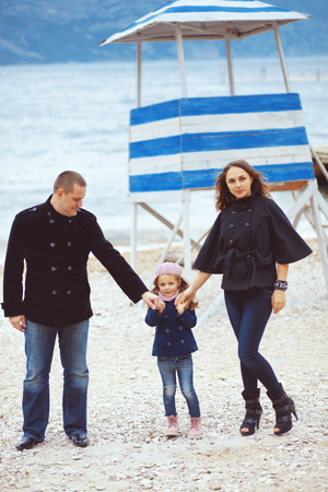 Portrait of happy young family walking with their child near sea in the city, still life photo photo