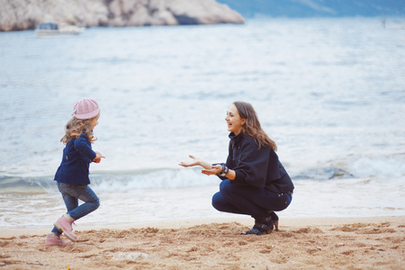 Portrait of mother with herdaughter playing on berth near sea in the city, still life photo photo