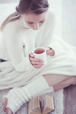 comfortable cozy: Soft portrait of teenage girl drinking hot coffee at home, instagram style toned