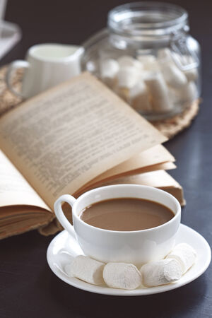 domestic scenes: Cup of hot coffee and vintage book on a table, selective focus