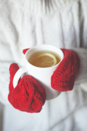 red gloves: Hands in gloves holding a cup of tea with lemon Stock Photo