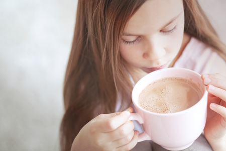 7 years old girl drinking hot cocoa from the big pink cup Stock Photo