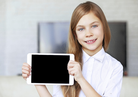 Child wearing formal wear holding tablet pc photo