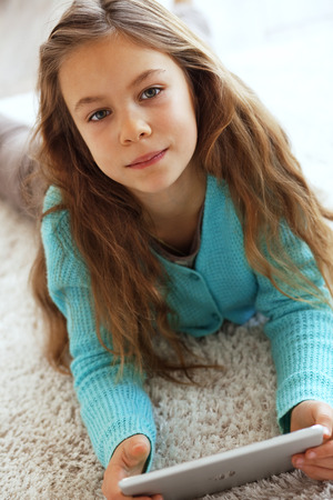 Child playing on tablet pc on a carpet at home photo