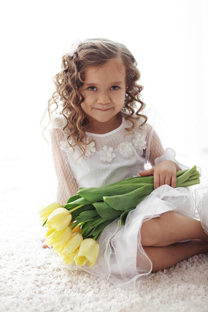 cinderella dress: Beautiful little princess wearing flower girl dress posing with the bouquet of spring tulips