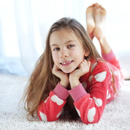 piedi nudi di bambine: Ritratto di bambino in morbido pigiama caldo sdraiati sul tappeto di casa