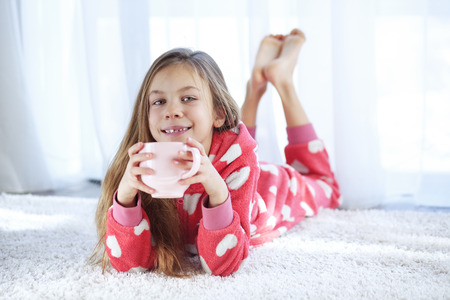Portrait of child in soft warm pajamas lying down on the carpet at home photo