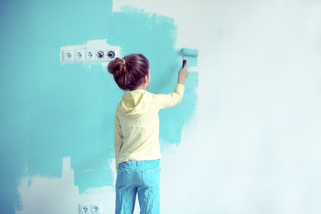 children painting: 7 years old girl painting the wall at home,  style toning