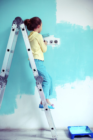 7 years old girl painting the wall at home, style toning photo