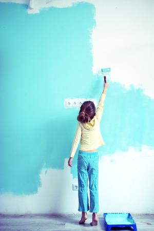 7 歳女児が自宅で壁を塗るスタイルの調子を整える 写真素材