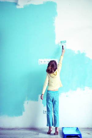 painting and decorating: 7 years old girl painting the wall at home, style toning Stock Photo