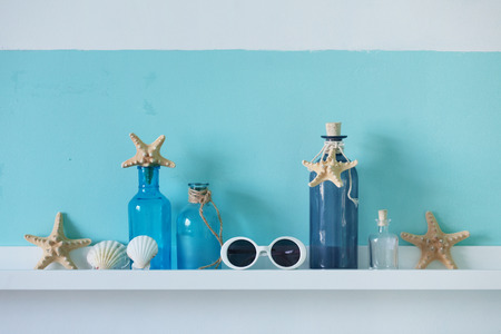 Idea of interior decoration with starfishes, glass bottles and wooden elements