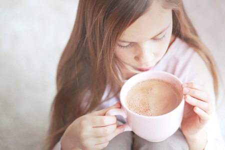 7 years old: 7 years old girl drinking hot cocoa from the big pink cup Stock Photo