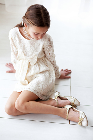 Fashion 7 years old model dressed in ivory lace dress pastel tone photo