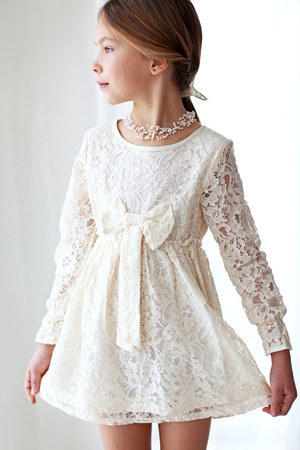 Fashion 7 years old model dressed in ivory lace dress pastel tone Banco de Imagens